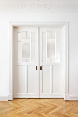 Witte oude dubbele schuifdeur met geweven glas in een historisch gebouw met stucwerk, kopieer ruimte