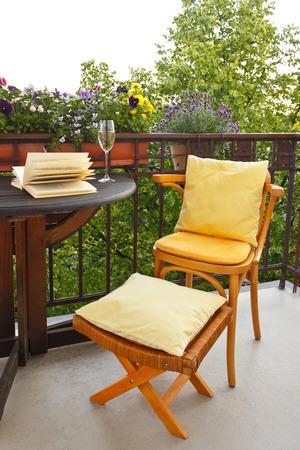 Balcón de una casa antigua con una silla y un taburete con cojines, libros y vino espumoso para relajarse en la luz de la tarde