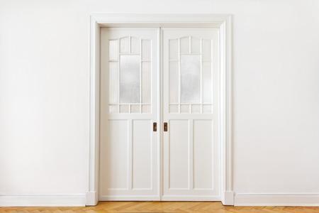wood door: Mur blanc avec une vieille porte coulissante double avec verre textur� dans un b�timent historique, copie, espace