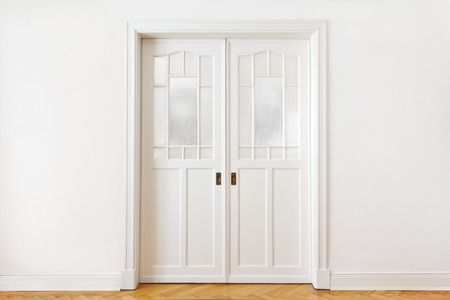 glass door: White wall with an old double sliding door with textured glass in an historic building, copy space