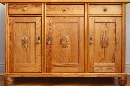 Vintage pine sideboard or cabinet with 3 drawers and three doors with wooden carvings, monochrome