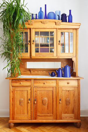 tidiness: Vintage pine kitchen cupboard with a plant, white tiles, doors, drawers and blue vases, frontal view