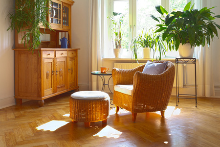 Sunny living room in warm colors with wicker armchair and stool, antique cupboard and plants