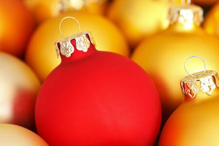 'yule tide': Close up of Christmas tree baubles in red and gold color, copy space