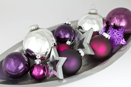 christmas tide: Christmas decoration bowl with tree balls and stars in silver, violet and purple on white