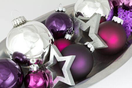 christmas tide: Colorful Christmas decoration of tree balls and and stars in silver and purple in a bowl