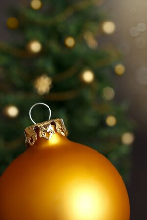 christmas tide: Gold Christmas ball ornament in front of a defocused Christmas tree with lots of shimmering lights, close up Stock Photo