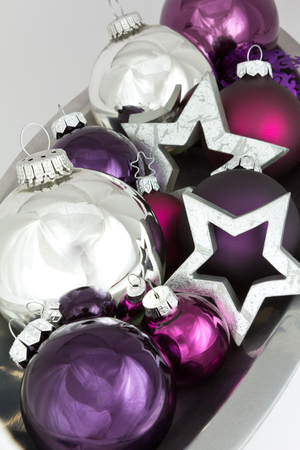 'yule tide': Christmas decoration with shiny silver stars and tree ball ornaments in violet and purple, colorful and bright Stock Photo