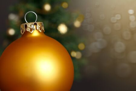 christmas tide: Shiny gold Christmas bauble in front of a Christmas tree and golden lights, copy space Stock Photo