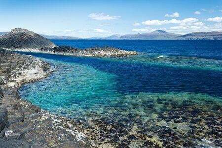 azul turqueza: roca negro con el agua azul turquesa del mar en la isla de Staffa Escocia, el espacio de copia