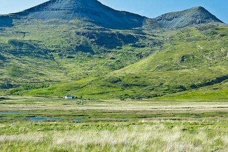 mull: Mountain with green slopes and grassland and a tiny house on Mull, Island of Scotland, copy space