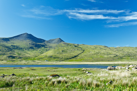 mull: Sunny landscape with a mountain or hill with grass and water in front of blue sky, Mull, Scotland, copyspace