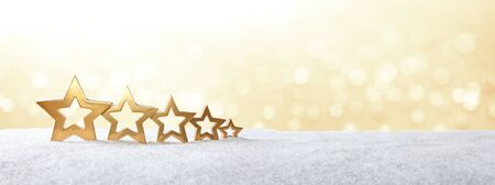 five stars: Five golden stars on snow in front of bright yellow light, christmas background, copy space, panorama format