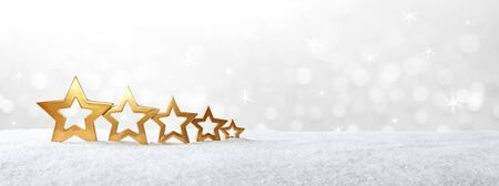 five stars: Five golden stars on snow in front of bright sparkling light, christmas background, copy space, banner
