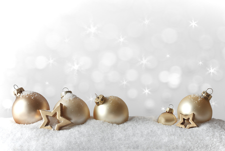 Golden christmas tree decoration, baubles and stars, on snow, bright background with snowflakes, copy space, vintage effect 免版税图像