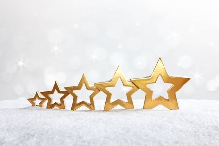 five stars: Five golden stars on snow in front of sparkling lights with snowflakes, background, copy space