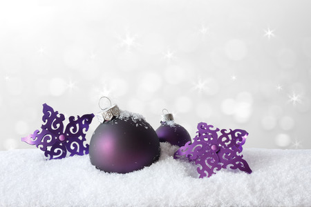 happy holidays text: Purple christmas tree decoration, baubles and stars, on snow, background, copy or text space Stock Photo