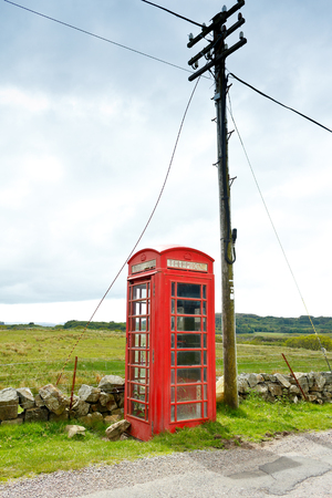 antique booth: Old red telephone booth with a pole at the coast of the scottish island Mull, copy space Stock Photo