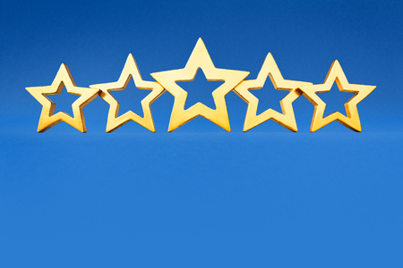 five stars: Five golden shining stars on blue background, symbol for classification, copy or text space