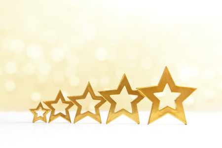 hotel reviews: Five golden shining stars in ascending order on white and yellow sparkling background, copy space