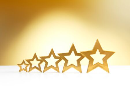hotel reviews: Five golden shining stars in ascending order on white and yellow background with a spot light, copy space