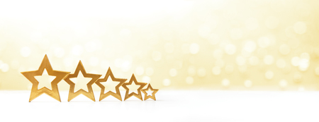 award background: Five golden shining stars on white and yellow sparkling background, copy space, banner format Stock Photo