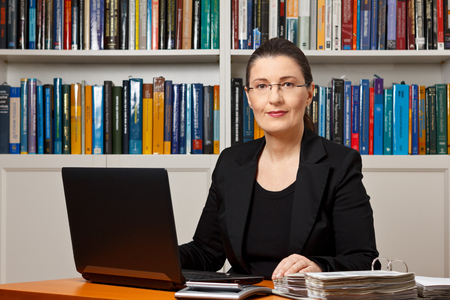 Volwassen vrouw in een kantoor of bibliotheek met laptop, rekenmachine en bestanden bindmiddel, fiscale of financiële accountant, adviseur, adviseur of raadsman