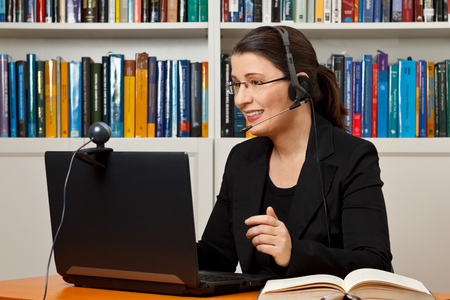 Mature woman with headset, laptop and webcam in front of a lot of books, giving online legal advice via a video call Archivio Fotografico