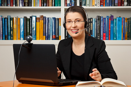 Smiling woman with headphone, computer and webcam in her office, consultant, adviser, teacher, online learning, business