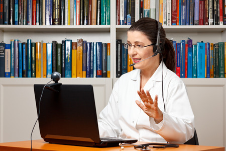 Doctor sitting with a headset or headphone at her desk in front of a computer with an attached camera and talking soothingly with a patient