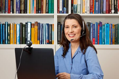 ip camera: Friendly smiling woman with computer, webcam and headphone at a callcenter, hotline or helpdesk
