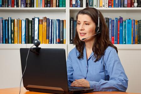 Telewerken vrouw met laptop, webcam en een hoofdtelefoon telefoneren visueel met een collega via internet
