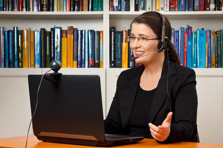 Leraar, docent of hoogleraar met hoofdtelefoon, laptop en camera in haar kantoor iets uit te leggen aan een online les of video lecture, webinar Stockfoto