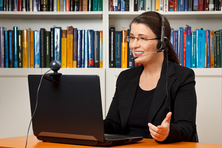 headset woman: Teacher, tutor or professor with headset, laptop and camera in her office explaining something at an online lesson or video lecture, webinar