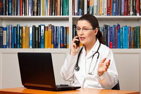 Woman doctor sitting at her desk in front of a computer and talking on the phone with a patient, telemedicine, health hotline, consultation