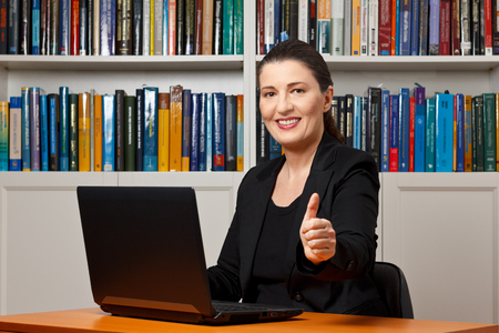 business symbol: Smiling woman in an office or library with her laptop holding her thumb up, symbol for success in business