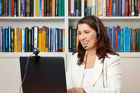 Lachend zakenvrouw in de voorkant van haar computer in haar kantoor met een videogesprek met haar familie thuis, voip