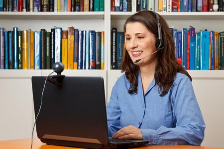 Mujer sonriente con el ordenador portátil, cámara y auriculares de vídeo llamadas telefónicas a través de Internet, skype