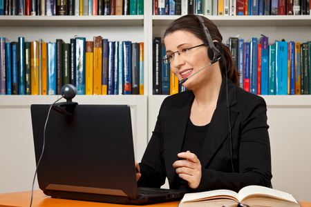 headset business: Female tutor or teacher with headset, computer and camera in her office talking with a student via video telephony, skype Stock Photo