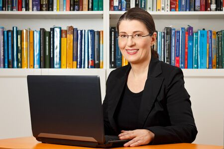 Friendly smiling woman in front of her laptop in a library, teacher, tutor, professor, consultant, consultancy