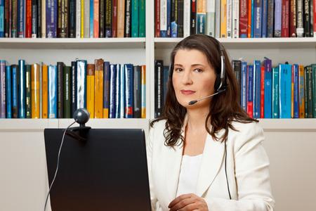 Midden oude vrouw met hoofdtelefoon in de voorkant van haar computer met webcam in een bibliotheek, adviseur, docent, tutor, online cursus Stockfoto