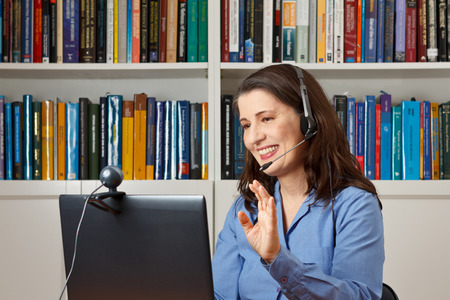 Smiling woman in her office with laptop, camera and headset telephoning with her children via the internet Standard-Bild