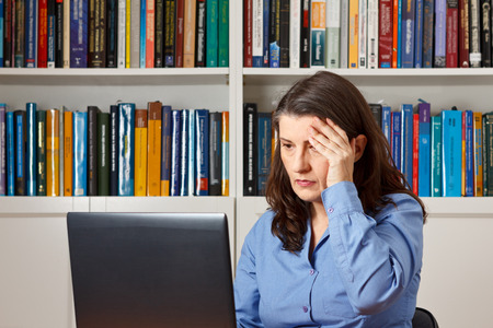 Mature woman in front of a computer in the office pressing a hand at her forehead, headache, migraine, stress