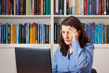 Rijpe vrouw in de voorkant van een computer in het kantoor het indrukken van een hand op haar voorhoofd, hoofdpijn, migraine, stress