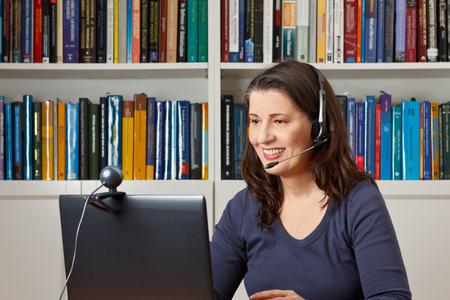 Middle aged woman with computer, headset and webcam talking with friends via viewphone