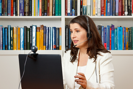 Teacher or tutor of a distance university giving an online lecture or webinar her office, mooc Archivio Fotografico