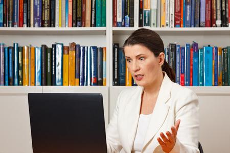 Mujer de negocios de mediana edad mirando sorprendido por su computadora en su oficina, el estrés, la frustración, la crisis