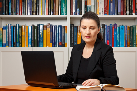 Mature woman in an office or library with her laptop reading in a book, advocate, lawyer, teacher, prof, historian, psychologist, diplomat