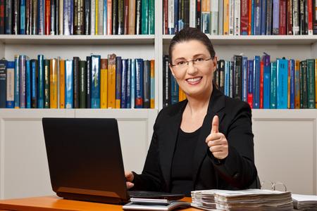 Lachende vrouw met computer, rekenmachine, file bindmiddel en thumbs up, best, bovenkant financieel of fiscaal adviseur, adviseur, adviseur