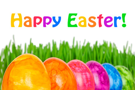 Row of 6 colorful Easter Eggs in front of green grass, text Happy Easter, in vivid rainbow colors Imagens